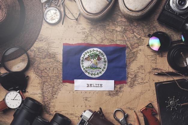Belize-flagge zwischen dem zubehör des reisenden auf alter weinlese-karte. obenliegender schuss