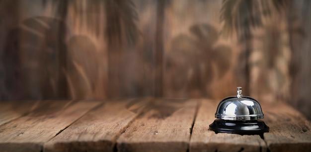 Bell service am sommer mit tropischen blättern schatten holztisch