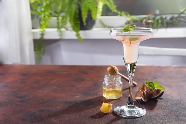 Bellini-cocktail mit pfirsich und feigen, honig auf braunem hintergrund über fenstern
