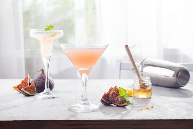 Bellini-cocktail mit pfirsich und feigen, honig auf hellem hintergrund über fenstern, kopienraum