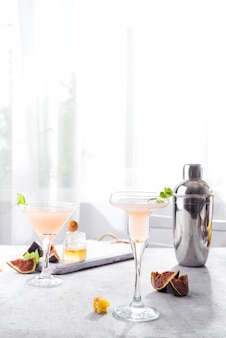 Bellini-cocktail mit pfirsich und feigen, honig auf hellem hintergrund über fenstern