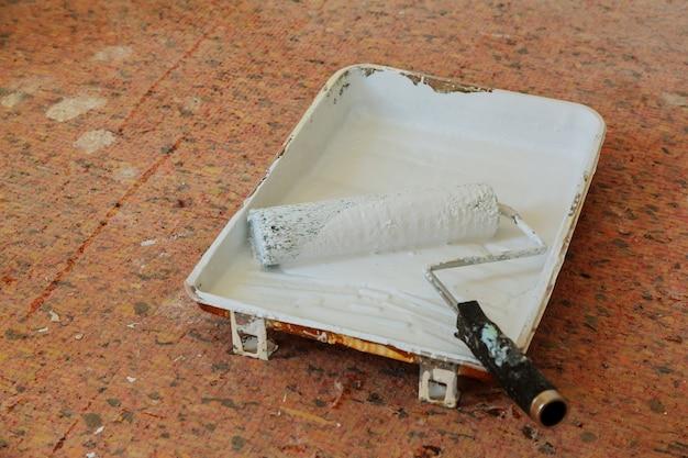 Bemalen einer rauen wand mit einer anstrichrolle. das bild enthält eine wand in einem neuen gebäude als hintergrund und farbroller
