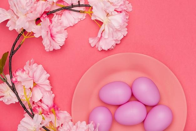 Bemalte eier auf teller mit blume daneben