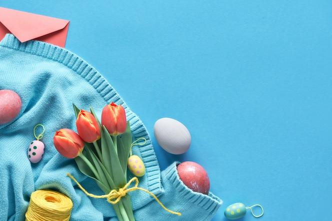 Bemalte eier, ein strauß orangefarbener tulpen und ein grußumschlag auf einem mintfarbenen baumwollpullover