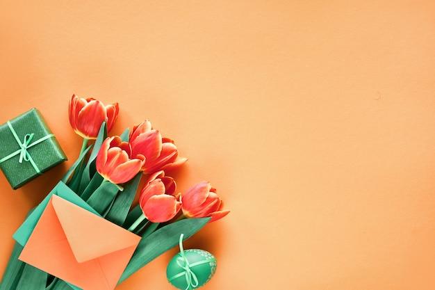 Bemalte eier, geschenkkarte, umschlag und geschenkboxen. ostern-ebene legen auf orange papier mit kopieraum