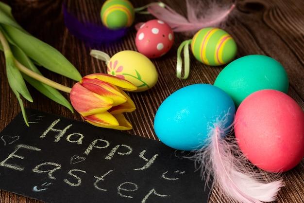 Bemalte eier in der nähe des schildes mit der aufschrift frohe ostern, federn und tulpenblume