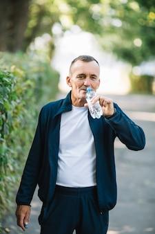 Bemannen sie anhebende flasche zum mund, um wasser zu trinken