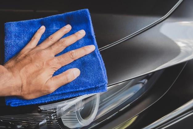 Bemannen sie asiatische inspektions- und reinigungsausrüstungsautowäsche mit grauem auto für das säubern zur qualität zum kunden auf autosalon des autotransportautotransport-automobilbildes.