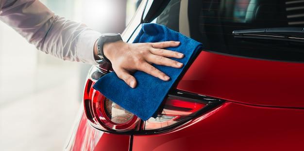 Bemannen sie asiatischen inspektionsscheinwerfer und reinigungsausrüstungsautowäsche mit rotem auto für das säubern zur qualität zum kunden auf autosalon des autotransportautotransport-automobilbildes.