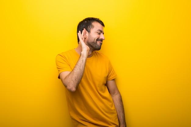 Bemannen sie auf der lokalisierten vibrierenden gelben farbe, die auf etwas hört, indem sie hand auf das ohr setzen