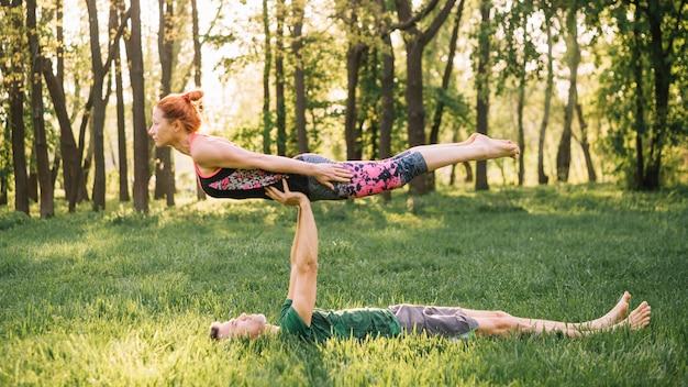 Bemannen sie balancierende frau auf seinem an beim üben von yoga im park