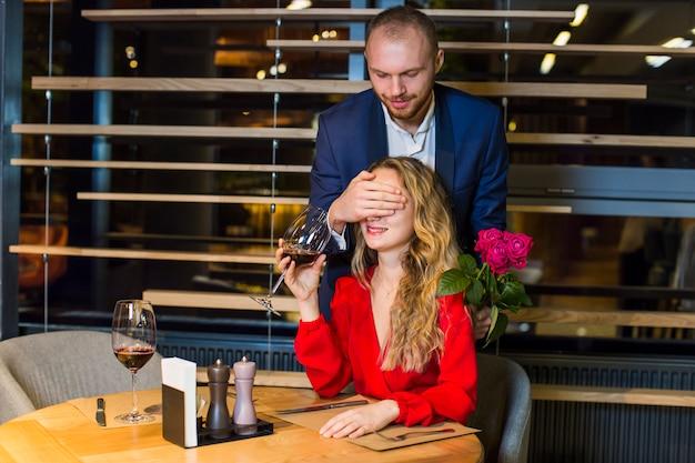 Bemannen sie bedeckungsaugen der frau mit der hand im restaurant