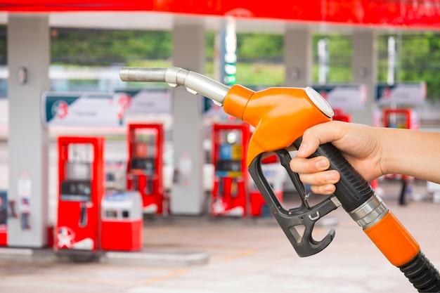 Bemannen sie brennstoffdüse halten, um kraftstoff im auto an der tankstelle hinzuzufügen.