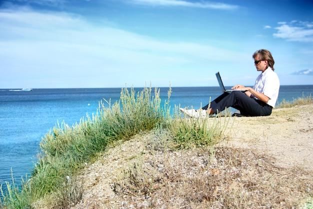 Bemannen sie das arbeiten mit dem laptop, der auf einem panoramischen seesichtspunkt gesetzt wird