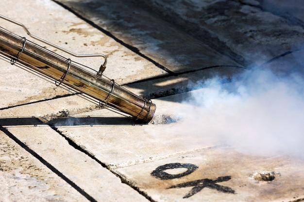 Bemannen sie das arbeiten mit einer rauchmaschine in einsteigeloch zur schädlingsbekämpfung