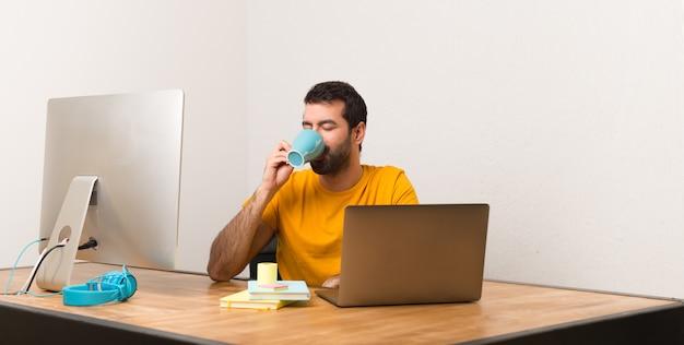 Bemannen sie das arbeiten mit laptot in einem büro, das einen tasse kaffee hält