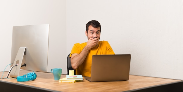 Bemannen sie das arbeiten mit laptot in einem büro, das mit dem finger auf jemand und das lachen zeigt
