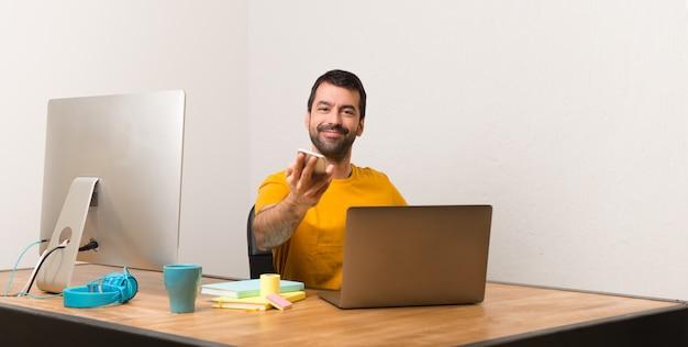 Bemannen sie das arbeiten mit laptot in einem büro, das mit mobile spricht