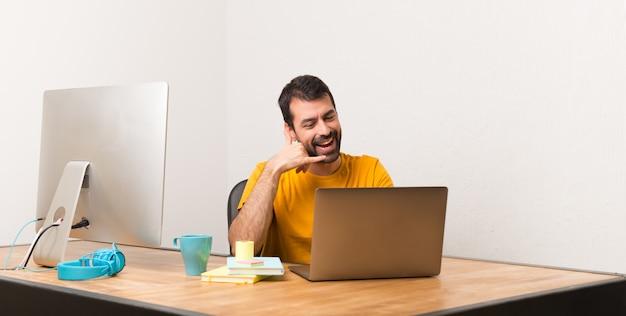 Bemannen sie das arbeiten mit laptot in einem büro, das telefongeste macht. ruf mich zurück zeichen