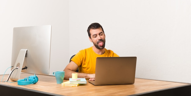 Bemannen sie das arbeiten mit laptot in einem büro, das zunge an der kamera zeigt, die lustigen blick hat
