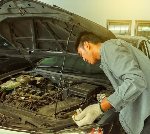 Bemannen sie das asiatische auto, das inspektion überprüft, um ein foto für verlegenheit reparatur zu machen