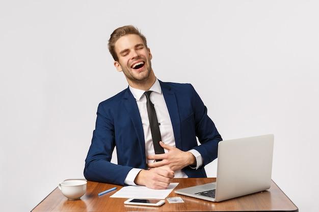 Bemannen sie das aufpassen von lustigen videos online beim sitzen des büros während der arbeitszeit. attraktiver geschäftsmann im sitzenden schreibtisch der klassischen klage lachend über komödie oder meme in der laptopanzeige, weißer hintergrund