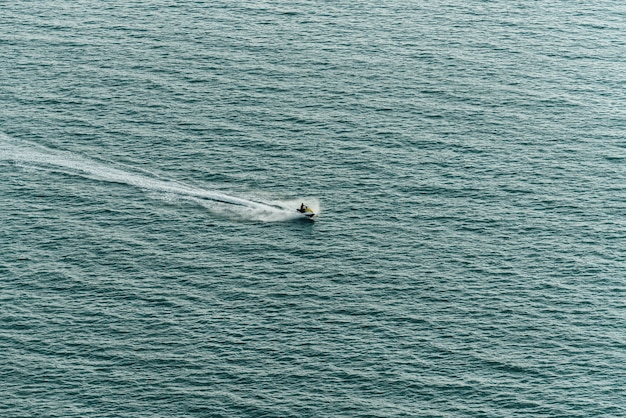 Bemannen sie das befreien von jetski auf dem meer mit spritzwasserspur auf der seeoberfläche nahe pattaya-strand.
