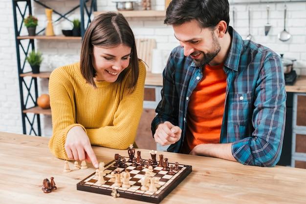 Bemannen sie das betrachten der frau, die das schachspiel auf hölzernem schreibtisch spielt