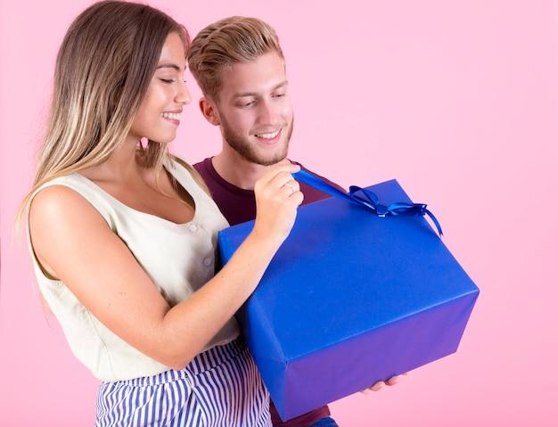 Bemannen sie das betrachten der lächelnden frau, die blaue geschenkbox gegen rosa hintergrund öffnet