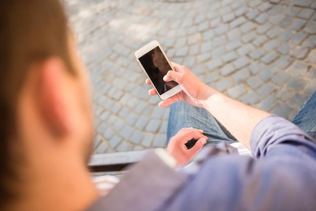 Bemannen sie das betrachten des telefons und auf der bank an der stadtstraße sitzen.