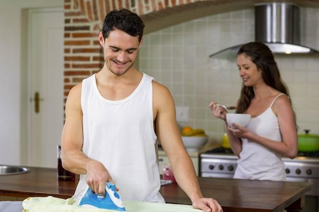 Bemannen sie das bügeln eines hemdes während frau, die im hintergrund frühstückt