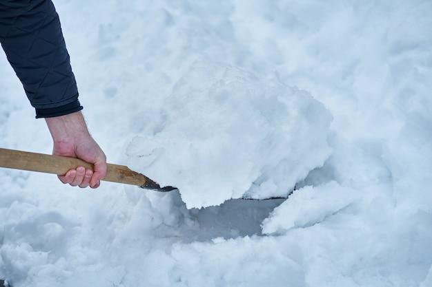 Bemannen sie das entfernen des schnees mit schaufel, seitenansicht des ländlichen winters