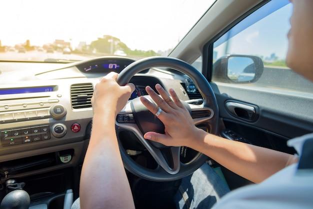 Bemannen sie das fahren eines autos mit den händen, die das lenkrad eines autos halten und das horn hupen.