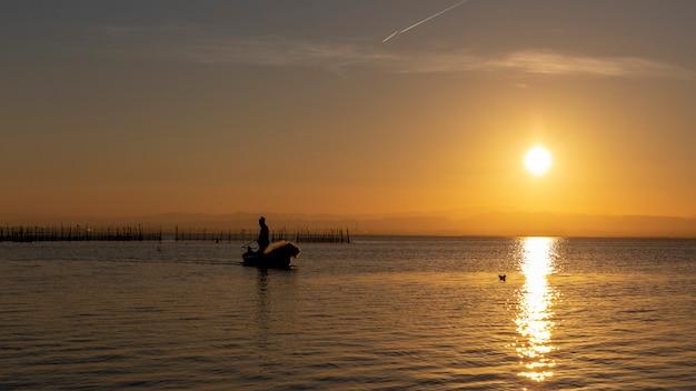 Bemannen sie das fischen in einem boot bei sonnenuntergang in albufera von valencia.
