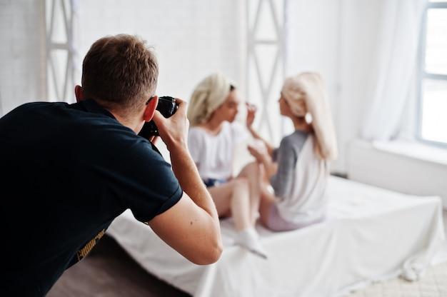 Bemannen sie das fotografschießen auf mädchen des studios zwei, während sie ihre eigene maskencreme machen. professioneller fotograf bei der arbeit.