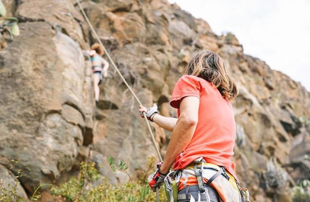 Bemannen sie das geben der unterstützung zur frau, die oben auf gebirgsklippe klettert