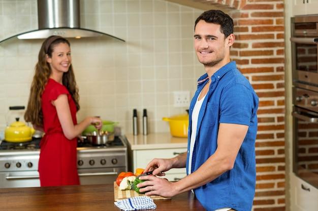 Bemannen sie das hacken des gemüses und der frau, die zu hause auf ofen in der küche kochen