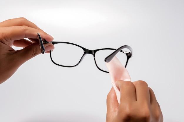 Bemannen sie das halten der brille des schwarzen auges mit dem glänzenden schwarzen rahmen, der auf weiß lokalisiert wird