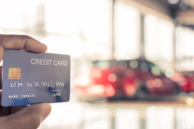 Bemannen sie das halten der kreditkarte für das unscharfe bokeh hintergrund-e-shopping, das digitales, verbraucherkaufeinkaufsinternet-on-line-bild vermarktet