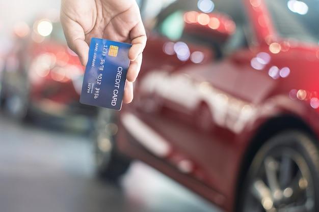 Bemannen sie das halten der kreditkarte für das unscharfe digitale bokeh hintergrund-e-shopping-marketing