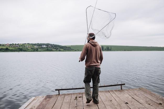 Bemannen sie das halten des fischernetzes und der stange, die auf hölzernem pier vor see stehen
