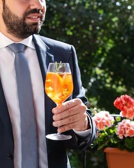 Bemannen sie das halten des glases mit italienischem aperol spritz, alkoholisches cocktail