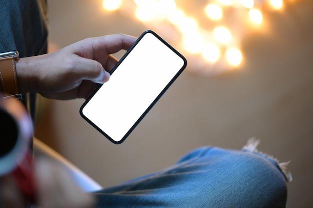 Bemannen sie das halten des intelligenten mobiltelefons nachts mit unscharfem hintergrund