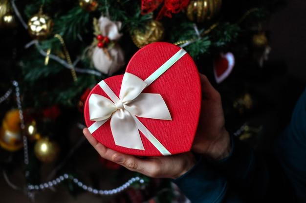 Bemannen sie das halten des roten herzpräsentkartons in seinen händen mit weihnachtsbaumdekoration