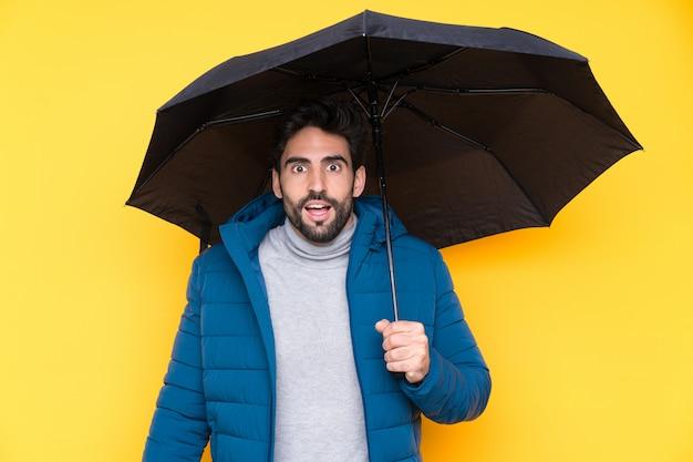 Bemannen sie das halten eines regenschirmes über lokalisierter gelber wand mit überraschung und entsetztem gesichtsausdruck