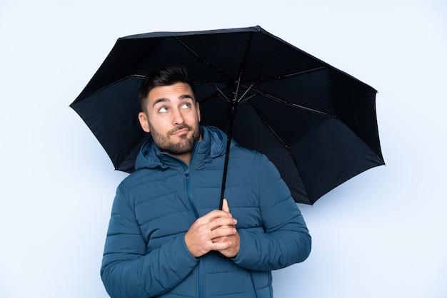 Bemannen sie das halten eines regenschirmes über lokalisierter wand mit traurigem ausdruck