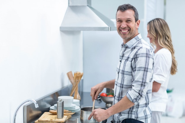 Bemannen sie das helfen der schwangeren frau, lebensmittel in der küche zuzubereiten