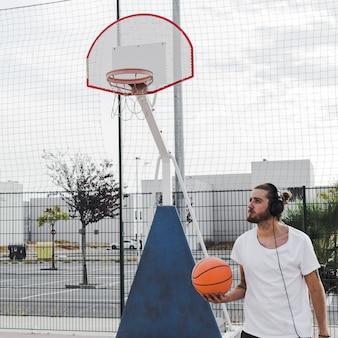 Bemannen sie das hören musik auf dem kopfhörer, der vor gericht basketball hält