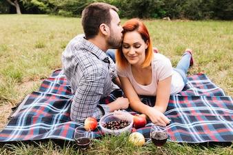 Bemannen Sie das Küssen ihrer Freundin, die auf Decke über grünem Gras mit Früchten liegt