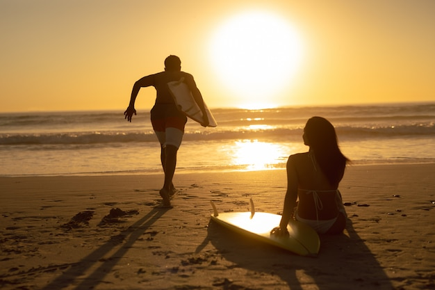Bemannen sie das laufen mit surfbrett während die frau, die auf dem strand während des sonnenuntergangs sich entspannt